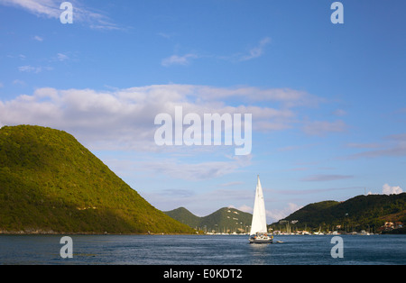 A sailboat cruises on the blue calm ocean in the British Virgin Islands. - Stock Photo