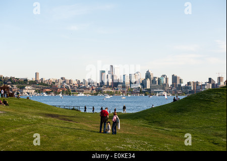 Families and friends gather at Gas Works Park which overlooks Lake Union and the Seattle Skyline. - Stock Photo