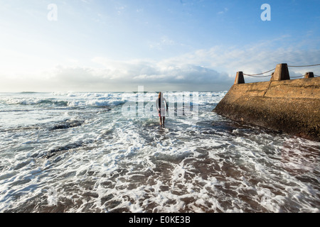Surfing surfer unidentified on beach entering walking towards the ocean waves - Stock Photo