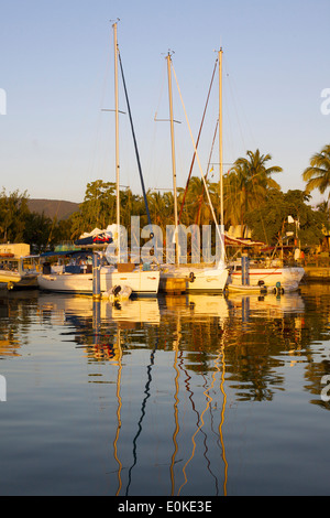 Sailboats docked at a yacht club reflect in the calm water at sunset. - Stock Photo