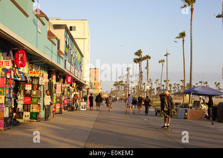 Shoppers walk and a young man skateboards down the sunny Venice Beach Boardwalk in Los Angeles, California. - Stock Photo