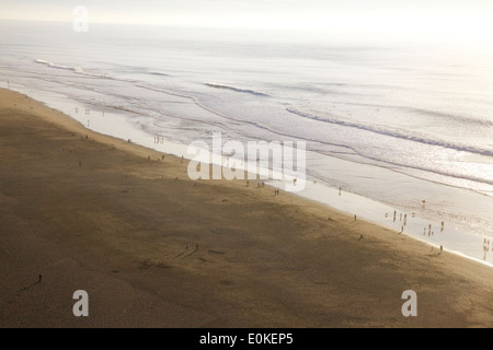 A view from above of people enjoying the afternoon along the water's edge at Ocean Beach in San Francisco. - Stock Photo