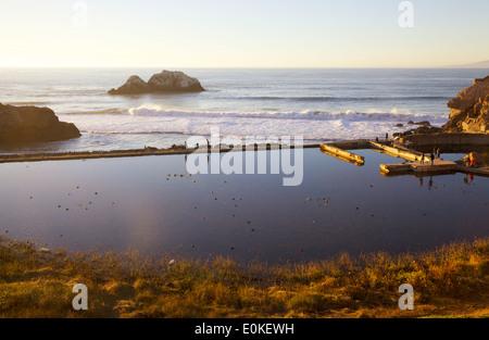 People walk along the sea wall at the Sutro Bath Ruins at Lands End in San Francisco, California. - Stock Photo