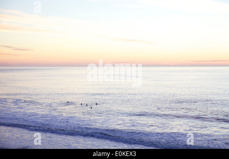 Surfers in the distance waiting patiently to catch a wave are silhouetted against the sunset on the horizon. - Stock Photo