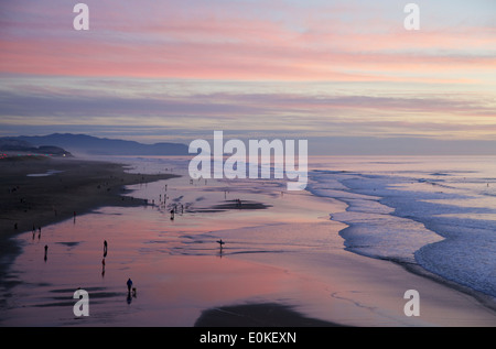 People walking along the shore are silhouetted against a brilliant sunset with colors of blue, pink and purple. - Stock Photo