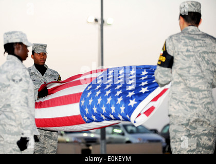 SOUTHWEST ASIA - Airmen from the 386th Air Expeditionary Wing honor guard fold the American flag during a Retreat - Stock Photo