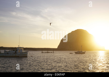 Boats float on the water as the sun sets behind Morro Bay Rock in Morro Bay, California - Stock Photo