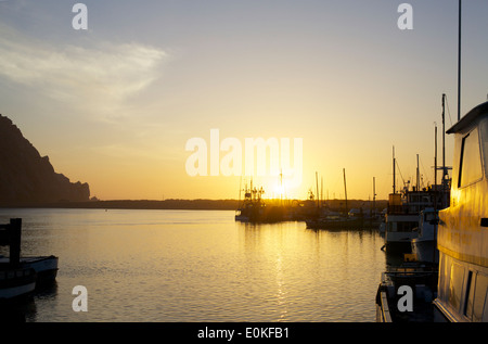 Boats float on the water as the sun sets on the horizon in Morro Bay, California. - Stock Photo