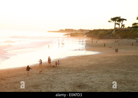 A girl walks her dog and beach goers enjoy the afternoon light on the coast along Steamers Lane in Santa Cruz, California. - Stock Photo