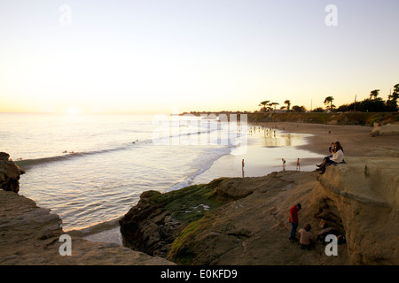 People hang out on the cliffs and take in the view as beach goers enjoy the sunset along Steamers Lane in Santa - Stock Photo