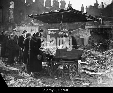 People buying food from a street cart among wreckage from the Blitz - Stock Photo