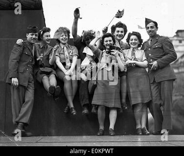 ATS and American soldiers cheer from one of the plinths in Trafalgar Square. 8/5/45 - Stock Photo