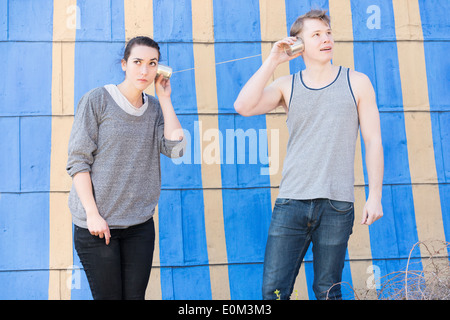 Young man and woman listening in a tin can phone  Conceptual image showing lack of communication and listening in - Stock Photo
