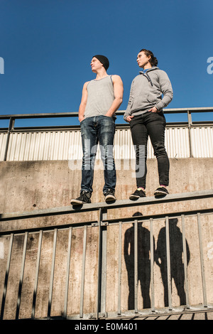Portrait of casual and relaxed young man and woman balancing on rail in urban area. - Stock Photo