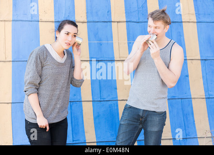 Young man talking in a tin can phone and woman listening. Conceptual image of communication and listening in a relationship. - Stock Photo