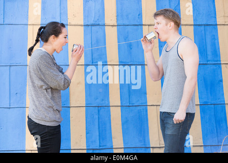 Young man and woman shouting  in a tin can phone Conceptual image showing anger and frustration in a relationship. - Stock Photo