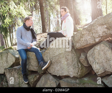 Young couple in nature resting on big rocks in woods during a trek. - Stock Photo