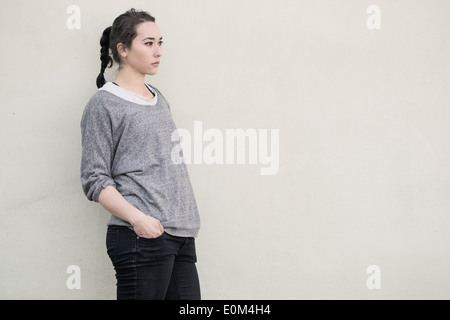 Portrait of young hispanic woman standing in front of wall. Pensive expression and looking away. - Stock Photo