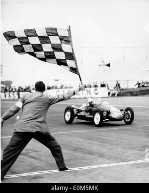 Stirling Moss crossing the finish line at Grand Prix in a Cooper - Stock Photo
