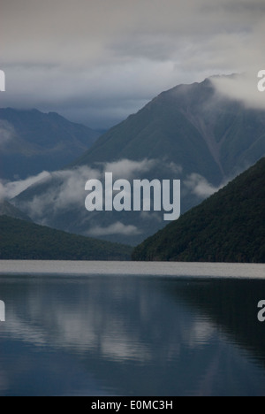 Clouds on mountains reflected in still lake, Lake Rotoiti, Nelson Lakes National Park, New Zealand - Stock Photo