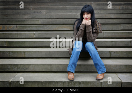 sad woman sitting on steps outside - Stock Photo