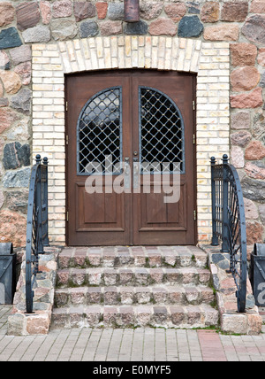 Front door of a old mansion with decorative metal handrail - Stock Photo
