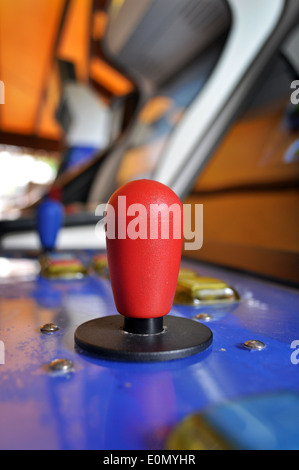 Joystick of a vintage arcade videogame in a public game room - Stock Photo