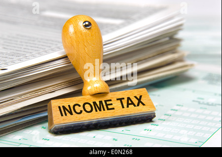income tax marked on rubber stamp - Stock Photo