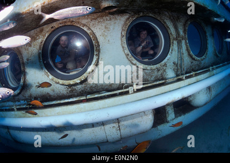 Tourists on Submarine Safaris' yellow sub underwater looking out of portholes, Tenerife - Stock Photo