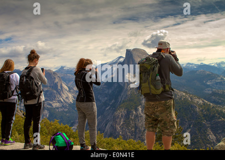 Visitors taking photo's and viewing the valley from Glacier point, Yosemite national park California USA - Stock Photo