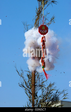 Asian firecrackers exploding at a lunar New Year festival tied to bamboo and thought to bring good luck and prosperity - Stock Photo