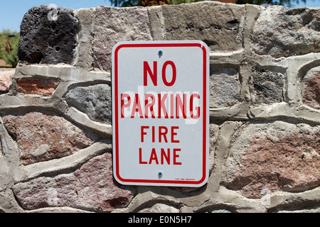 No Parking Fire Lane sign on a natural stonewall - Stock Photo
