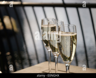 Three champagne glasses in a row on a wooden table - Stock Photo