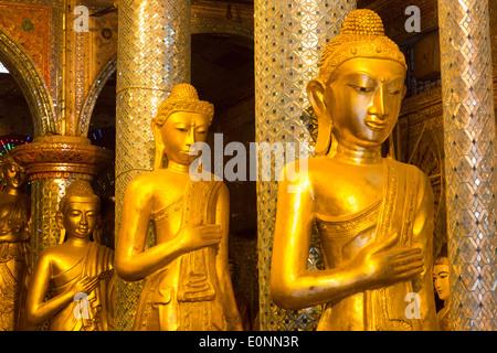 Golden Buddha statues at a shrine at the Shwedagon Pagoda in Yangon - Stock Photo