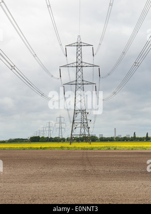 An English Landscape with electricity Pylons with Power Station in the distance and field of yellow rapeseed - Stock Photo