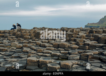 Couple sitting on the basalt stones at the Giant's Causeway, County Antrim, Northern Ireland, UK, a UNESCO World - Stock Photo