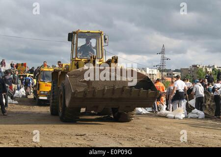 Belgrade, Serbia. 17th May, 2014. A forklift drives by as people build embankments by filling sacks with sand and - Stock Photo