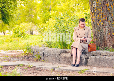 Elegant businesswoman sitting on a stone wall during a sunny spring day, and looking a message or dialing a number - Stock Photo