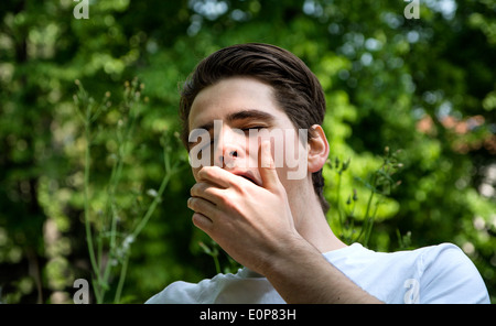 Bored or tired young man in a park yawning, covering mouth with his hand - Stock Photo