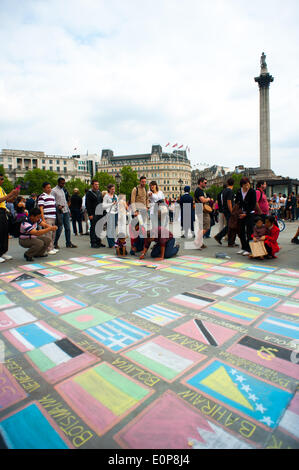 London, UK. 17th May, 2014. Man in Trafalgar Square drawing all the flags of the world. People could leave some - Stock Photo
