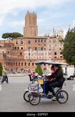 People riding in a bicycle taxi, the Forum, Rome Italy Europe - Stock Photo