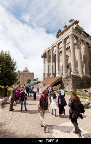 People walking along the Via Sacra in the Roman Forum, Rome, past the Temple of Antoninus and Faustina, ancient - Stock Photo