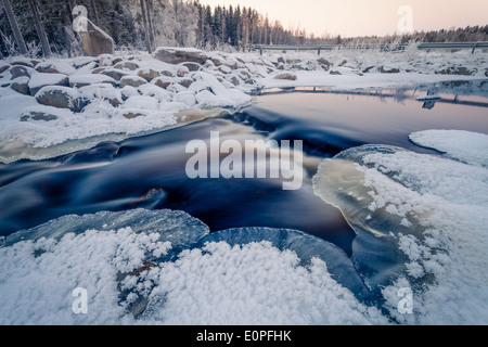 Beautiful colors of the sunset on the river in winter. - Stock Photo