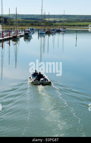 Coastal image showing a motorised boat moving through yarmouth harbour on the isle of wight in the uk - Stock Photo