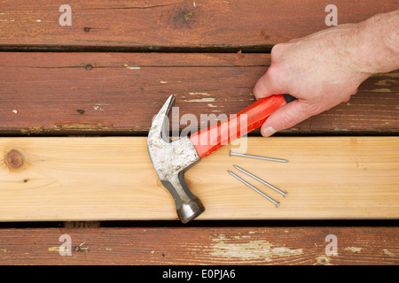 Horizontal photo of male hand picking up old hammer to install new cedar wood board into aging deck - Stock Photo