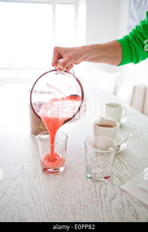 Closeup of delicious strawberry smoothie being poured into a glass from a large jug - Stock Photo