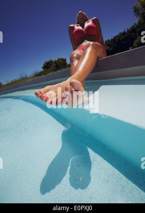 Low angle view of young woman wearing bikini enjoying the sun by the pool. Female model sunbathing by swimming pool. - Stock Photo