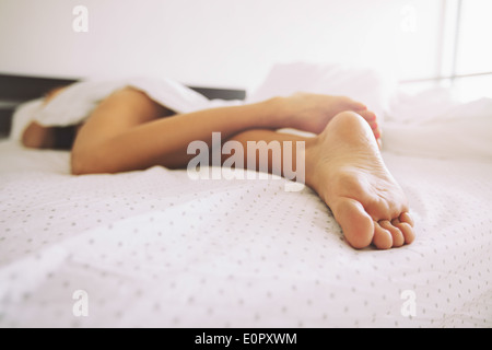 Young female sleeping in bed at home with focus on legs. Feet of woman lying on bed. - Stock Photo