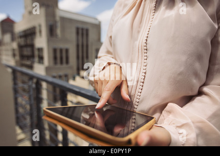 Close up image of young woman standing on balcony using digital tablet. Cropped image of female working on tablet - Stock Photo