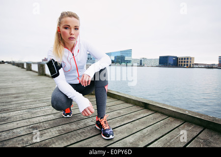 Young woman runner resting after running workout. Female fitness model crouching on sidewalk along river. Female - Stock Photo